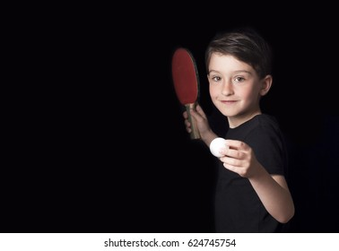Low key portrait of young boy isolated on black background. Ready to play table tennis