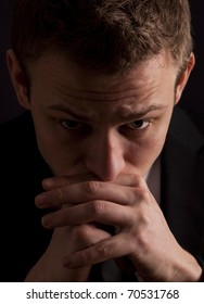 Low key portrait of a young businessman in deep thought, worrying or even praying.