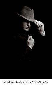 low key portrait of young gangster with hat in the darkness. Sepia toning.