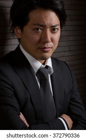 A low key portrait of a young Japanese man in a business suit with a serious expression on his face.