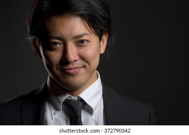 A low key portrait of a young Japanese man in a business suit with a hint of a smile on his face.