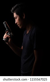 Low key portrait of young man with gun