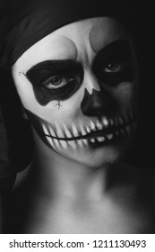 Low key portrait of young woman with skull make-up. Halloween concept.