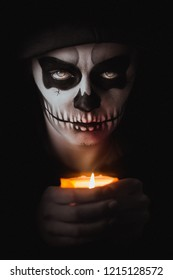 Low key portrait of young woman with skull make-up holding a candle. Halloween concept.
