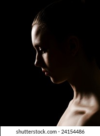 Low key portrait of a young woman with side lighting