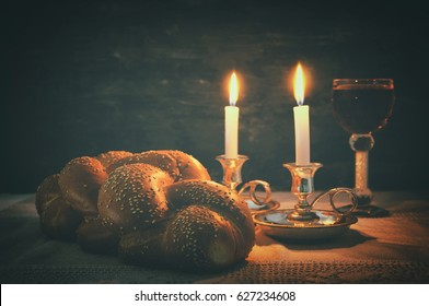 Low key shabbat image. challah bread, shabbat wine and candles on wooden table