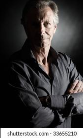 Low Key Shot of a Handsome Senior Man against Dark Background