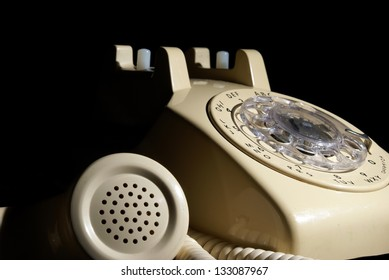 A low key shot of a rotary phone on hold.