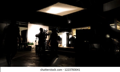 Low key silhouette lighting of VDO production behind the scenes which film crew team are setting up camera and set for shooting and waiting for movie director okay with the scenes in monitor.