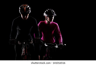 low key silhouette of a man and a  girl cyclists riding  bicycles on black background