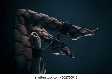Low key special toned photo of sexy female nude legs in net tights and hands binded with cuffs against dark background