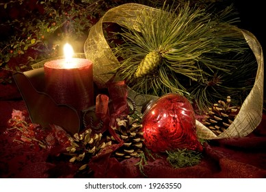 Low key still life of Christmas decorations in reds and greens.