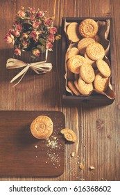 Low key still life with cookies in the box and dry roses on wooden board. Biscuits stack and one broken cookie with crumbs on cutting board.