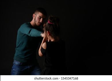 Low key studio photography. Black background. A man, a boy strikes, beats, attacks a girl, a child. Violence against children.