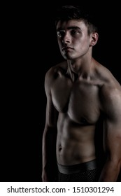 Low Key Studio Portrait Of A Shirtless Young Adult Caucasian Male Fitness Model