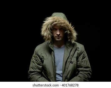 Low key studio portrait of suspicious young adult caucasian model wearing winter coat with hood on. Isolated on black.
