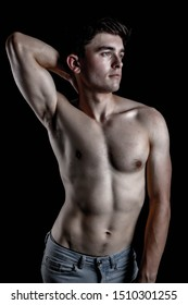 Low Key Studio Portrait Of A Young Adult Caucasian Male Shirtless Fitness Model Wearing Jeans