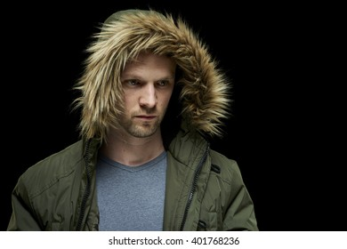 Low key studio portrait of young adult caucasian model wearing winter coat with hood on.