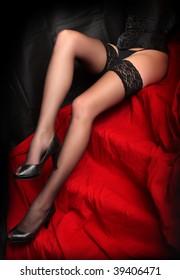 Low key studio shot beautiful slim legs in black nylons on a red background