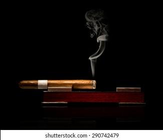 Low key studio shot of fine cigar burning in elegant ashtray with visible smoke on black background