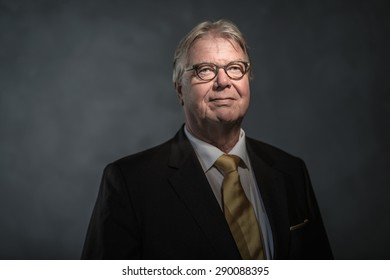Low key studio shot of positive senior man with glasses