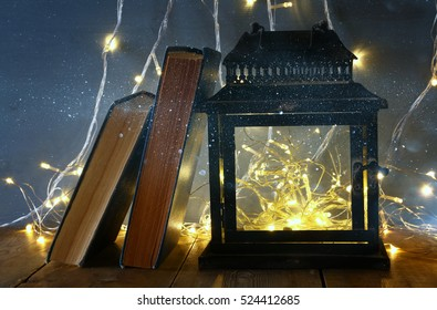 low key and vintage filtered image of fairy lights inside old lantern and antique books. Fairy tale concept