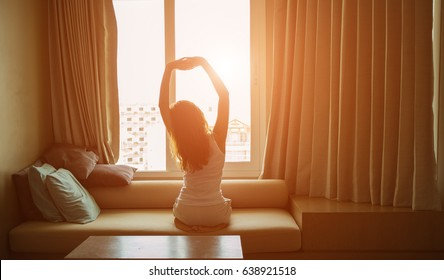 A low key of  woman waking up and stretching in the eary morning.