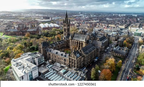 Low level aerial image over the autumn foliage of trees in Kelvingrove Park, Glasgow, to the gothic tower of Glasgow University with the cityscape behind.