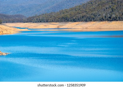 Low level dam on bright day with Australian bush in the background.