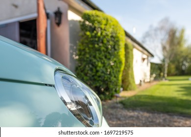 Low level view of a cars new style headlight. Seen parked in a private driveway, facing part of a large garden. A garage door can be seen opened on the left.