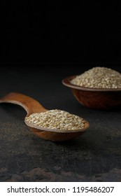 A low light image of a wooden spoon and bowl of sesame seeds with copy space for your text