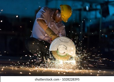 Low light image of Worker ware yellow helmet kneel use electric steel cutter machine. He has a Hard work in Factory or garage. Industry in construction site concept.