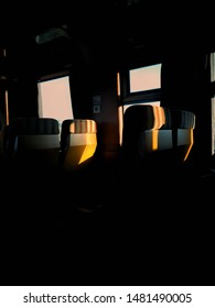 Low light photography of empty seats in an interior of train while taking a trip.