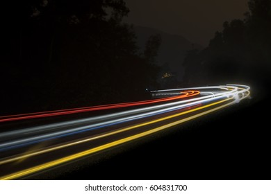 low light photography light trail at mountain highway, selective focus blurry and out of focus when viewed at full resolution