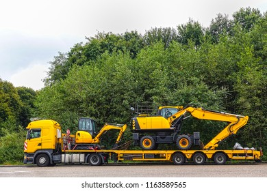 Low loader trailer carrying two excavators parking on a public truck parking area of a truck stop.