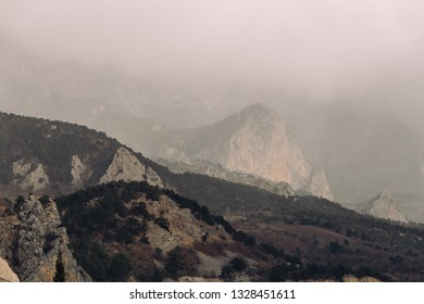 Low lying clouds on mountains in myst or dusk, dark dramatic and autumn depressive atmosphere, toned