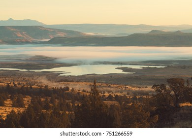 Low Lying Fog Over Lake and Mountains at Sunrise
