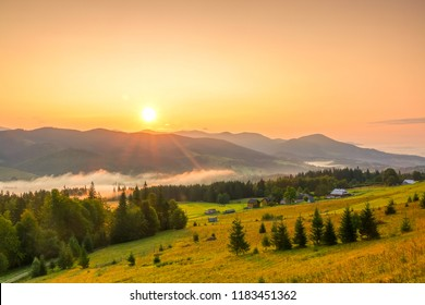 Low mountains and wooded valley. Summer. Several peasant houses. Morning mist in the valley. The sun rises in the cloudless sky