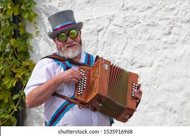 Low Newton-by-the-sea, Embleton, Northumberland, UK. 14th September, 2019, A portrait of an Morris Man with top hat playing a piano accordion in front of a white wall, wearing reflective sunglasses.