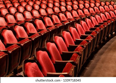 A low oblique view of the rows of red velvet seats in a restored vaudville theater.