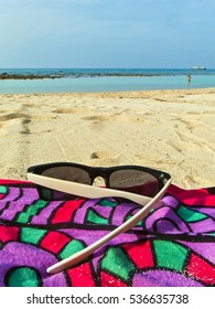 Low perspective shot of a colorful sarong on a sandy beach with a pair of sunglasses and a blue sky and ocean in the background - shot on Haad Khom or 'Coconut Beach' on Koh Pha Ngan, Thailand
