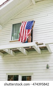 Low perspective of unrecognizable woman in underwear spreading American flag on balcony of white house
