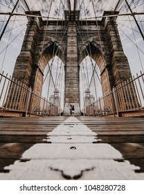 Low perspective wide angle shot of Brooklyn Bridge from New York City, NY, on a cloudy day