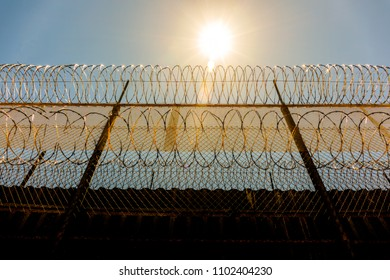 low POV of high razor wire topped boarder wall with the blazing sun in the sky