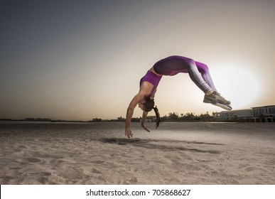 A low rear angle of Strong athletic, female sprinter as she does a back flip with sunrise and silhouettes of homes in the background