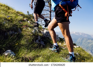 Low rear view of hikers walking up mountain