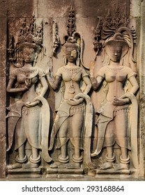 low relief in Angkor - three female statues in crowns - Apsarases, female spirits of clouds and waters in Hindu and Buddhist mythology