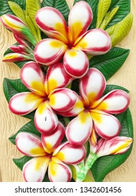 Low relief cement Thai style handcraft of plumeria on wall .