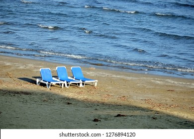 Low season. Empty sandy beach with three white plastic sun loungers on sand near before seacoast edge sea with small waves on bright sunny day