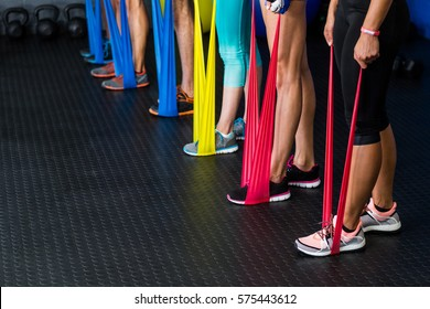Low section of athletes exercising with resistance band in fitness studio